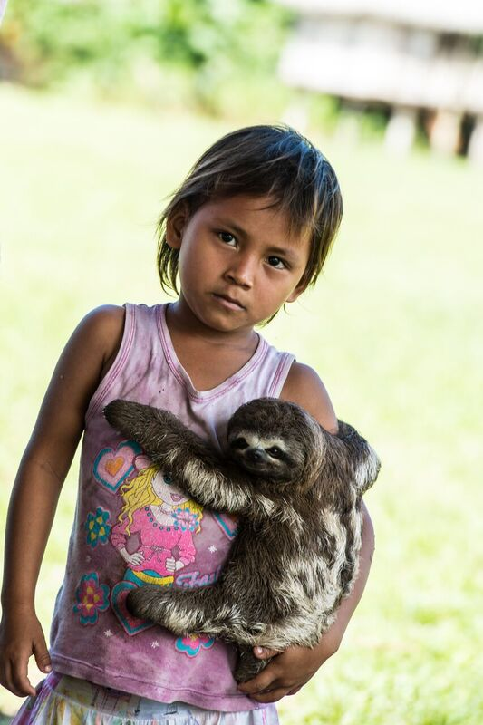 Peru Amazon Child with Baby Sloth, Photo: Brian Shepard