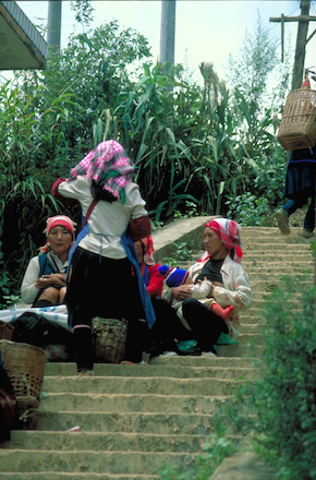 Chinese women sitting on steps returning from market.